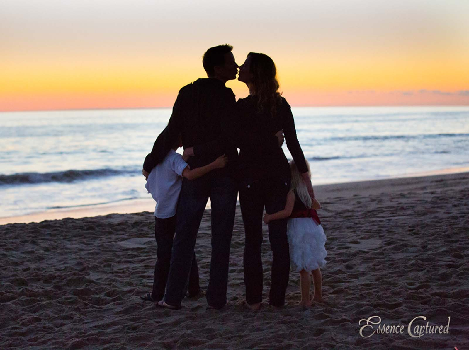 silhouette of family of four mom dad kiss walking on beach at sunset