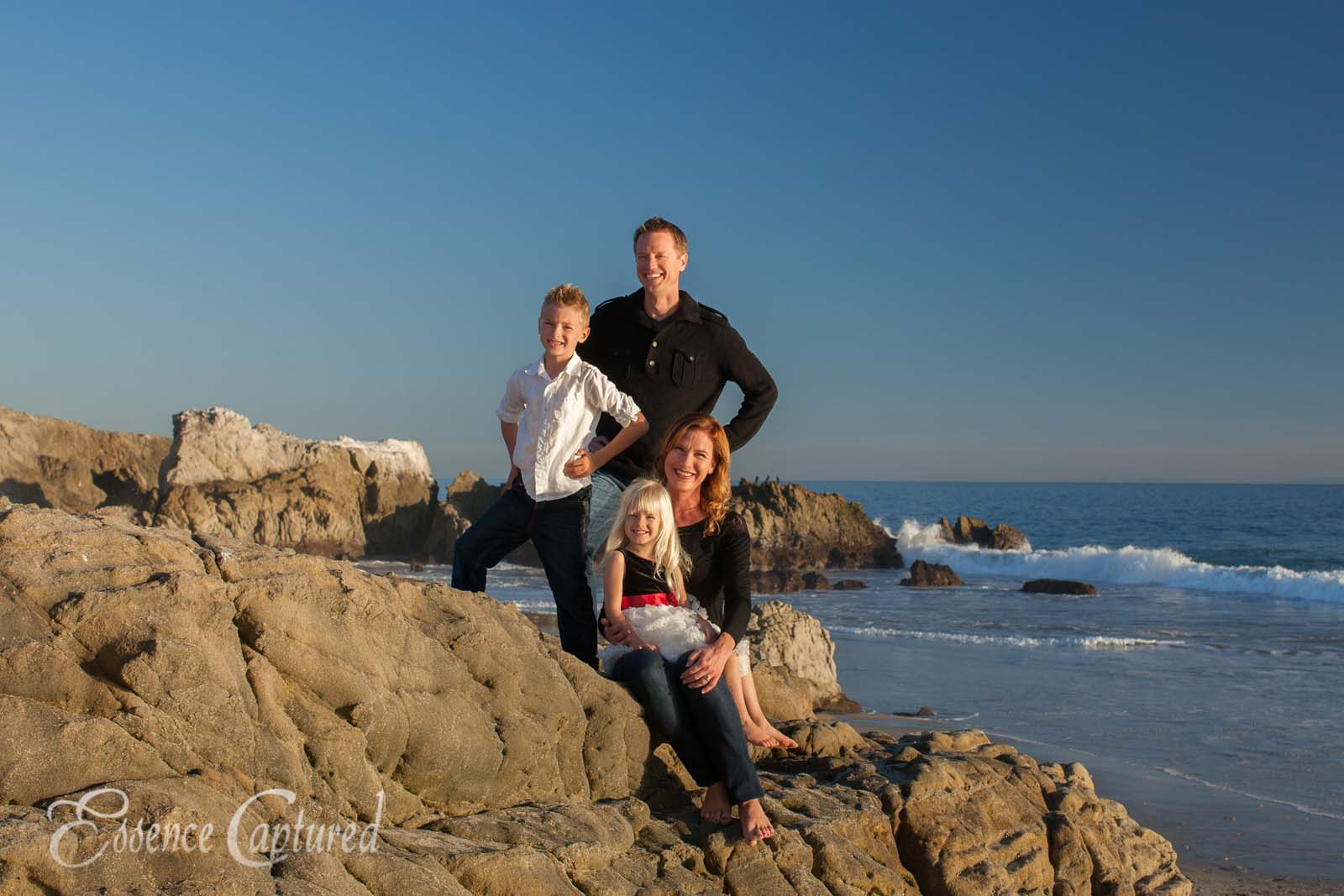 family portrait beach rocks ocean mom dad sister brother