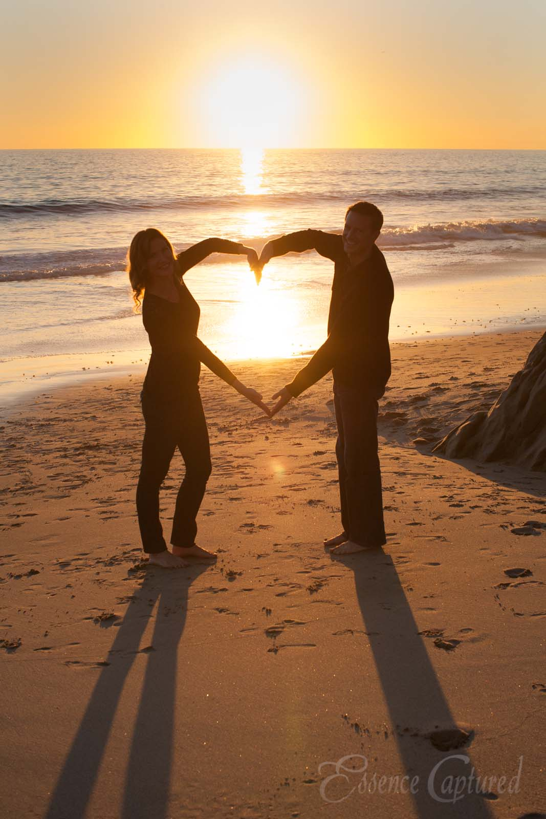 silhouette heart shape made by couples arms at sunset at beach