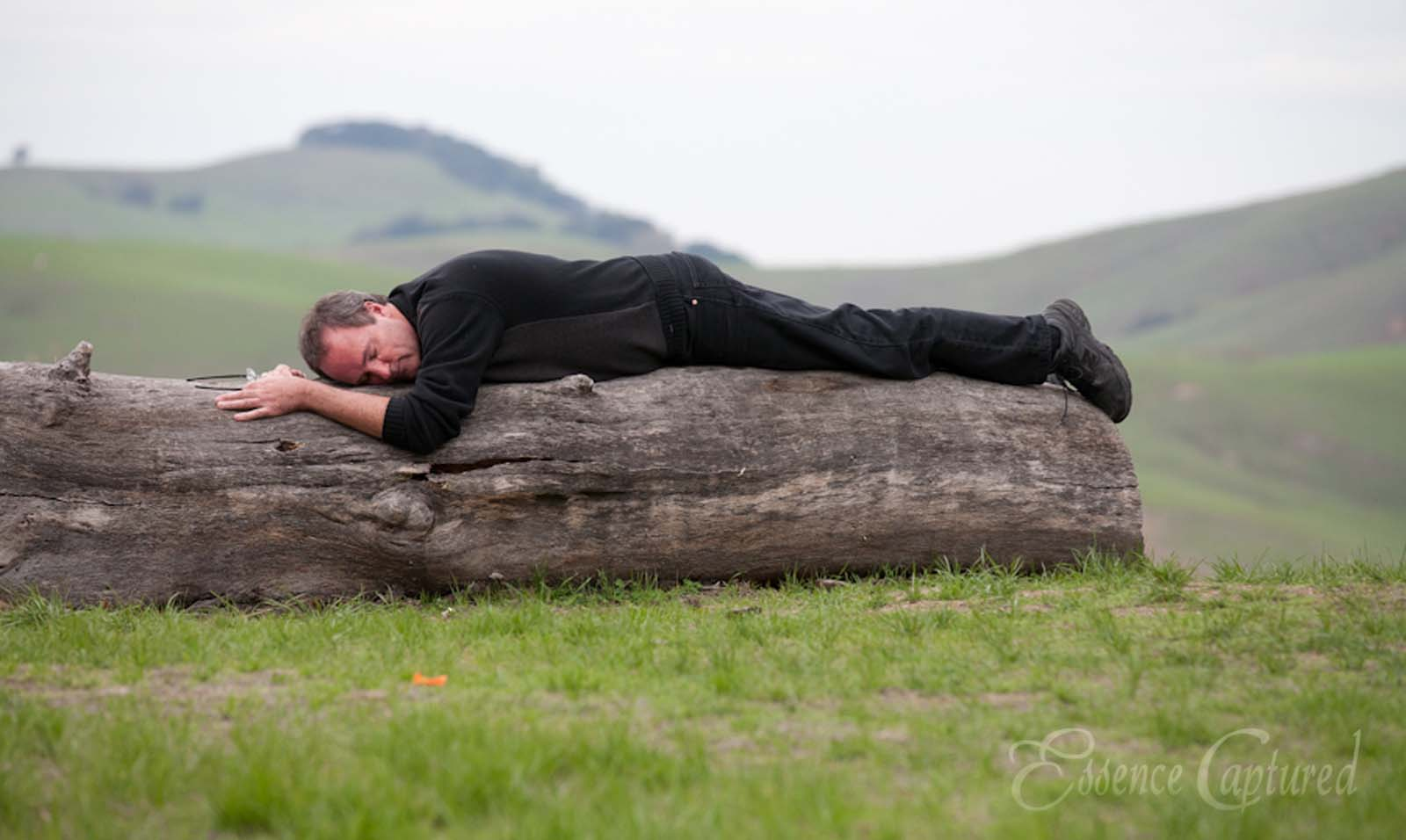 Man napping on tree log green grass foreground green hills background