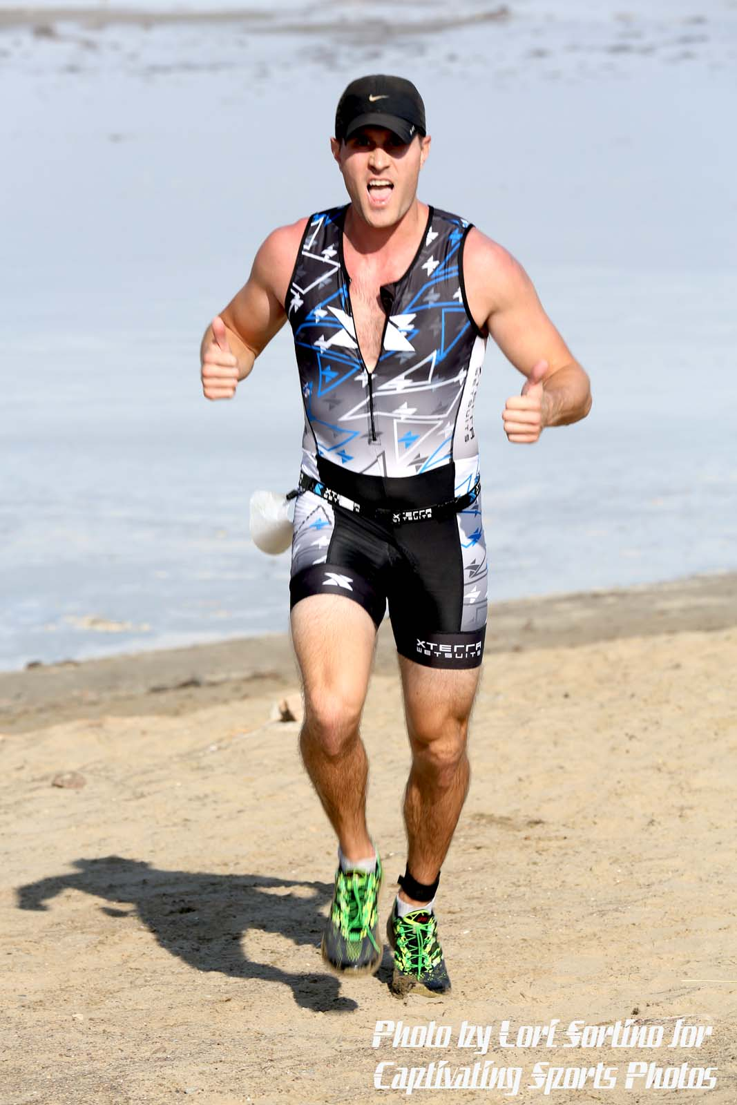 male triathlete running on beach thumbs up celebrating
