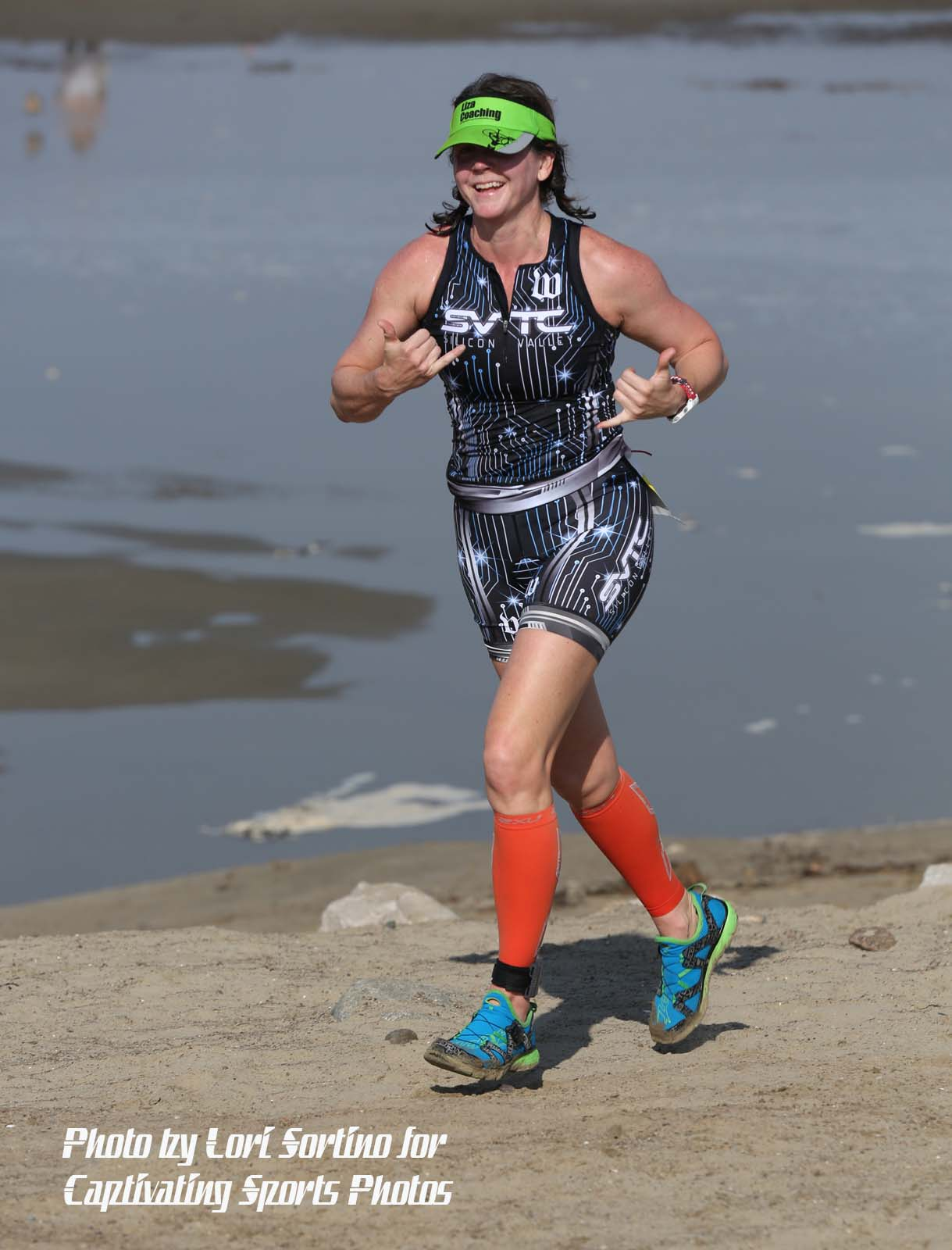 female triathlete running on beach gray jersey red socks Morro Bay Tri