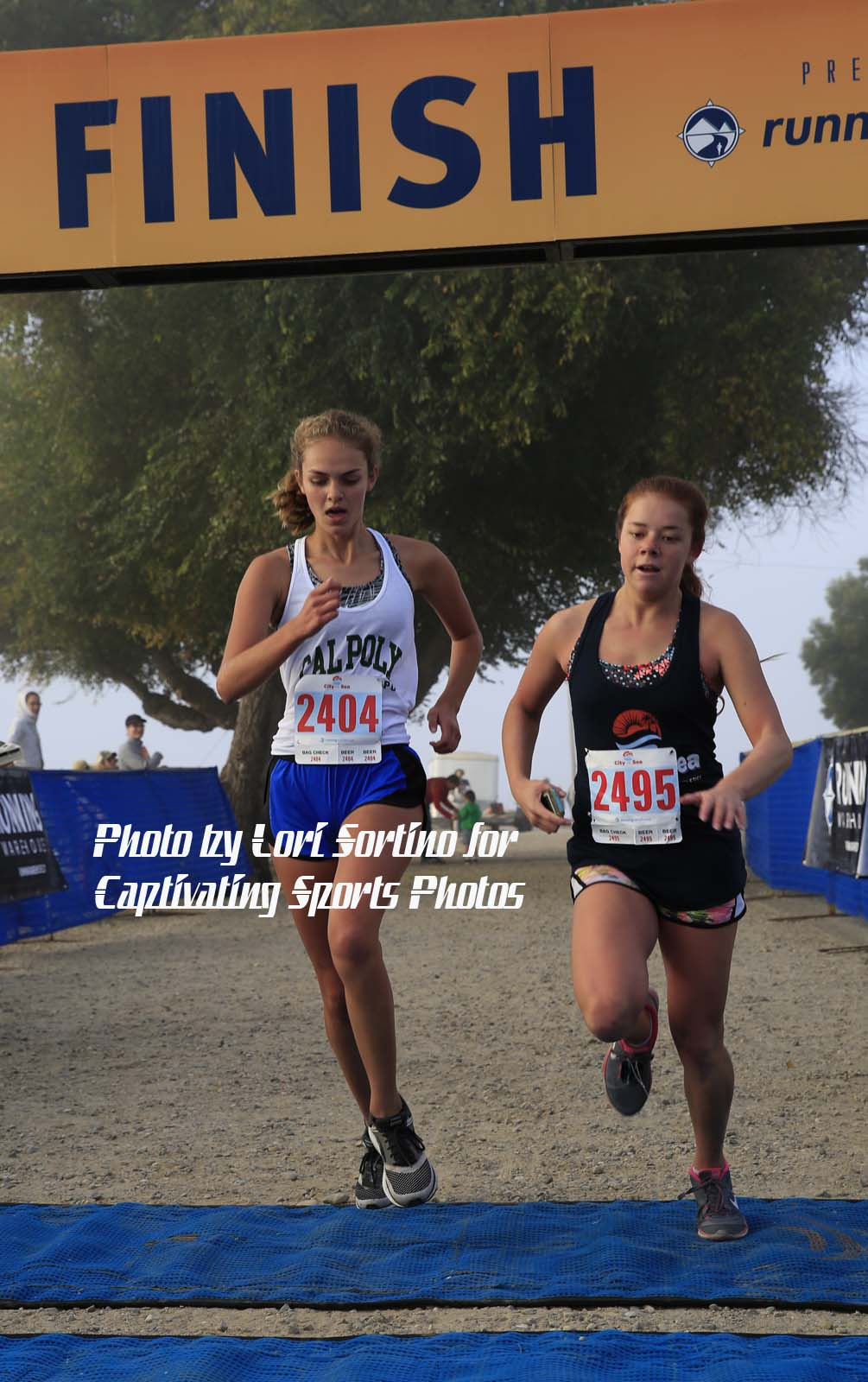 two female runners race to finish line City to Sea Shell Beach