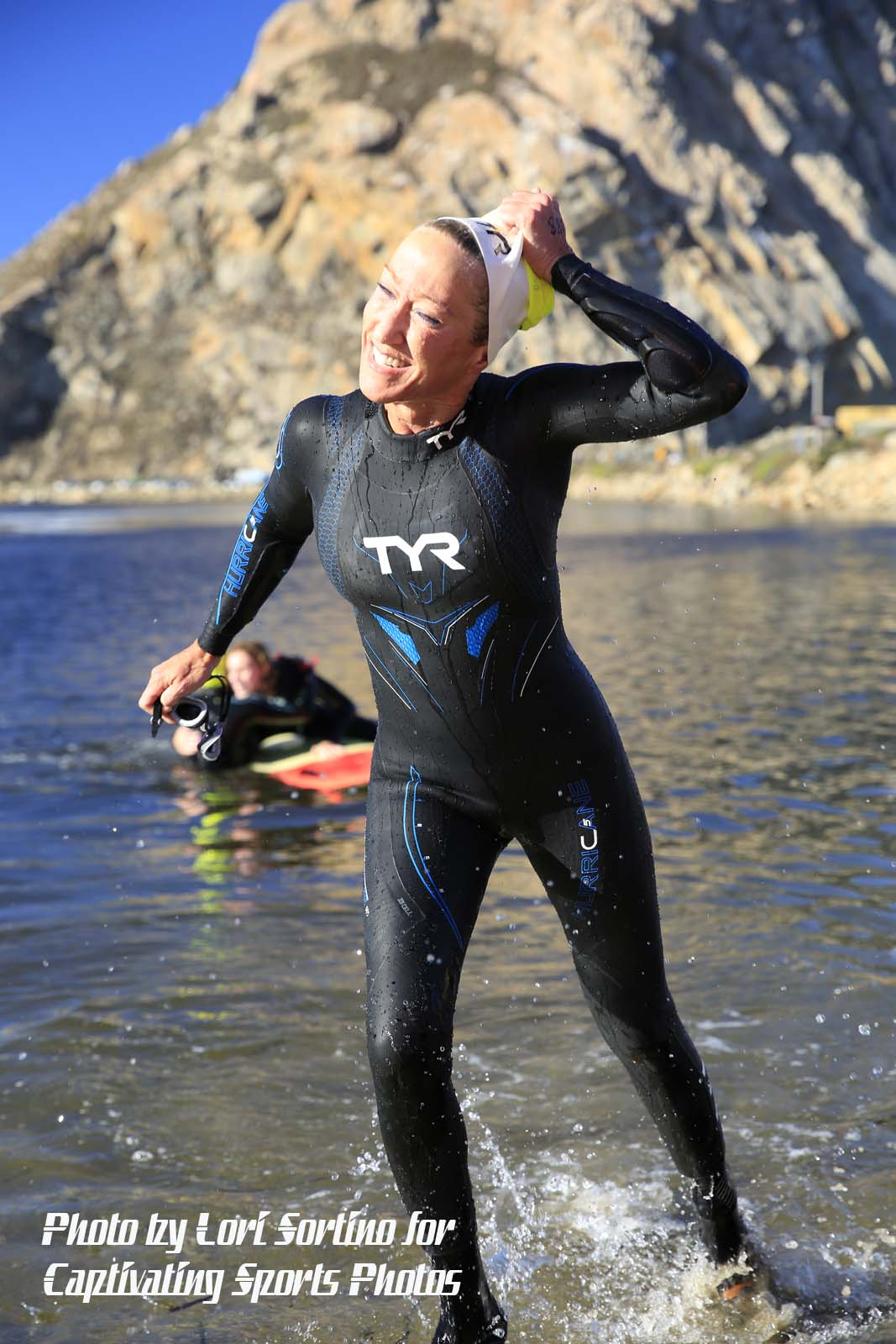 female takes swim cap off triathlon swim Morro Bay Tri