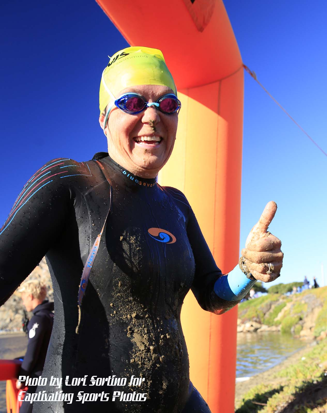 female triathlete thumbs up yellow swim cap swim goggles Morro Bay Tri