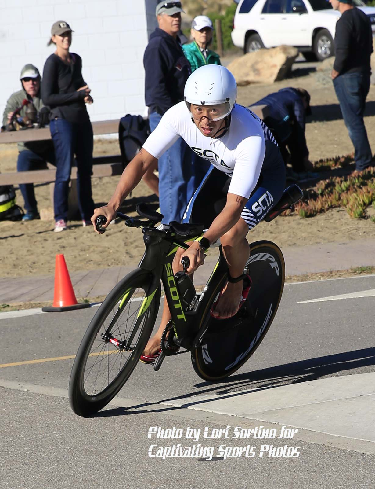male triathlete cycling rounding corner bare feet Morro Bay Tri
