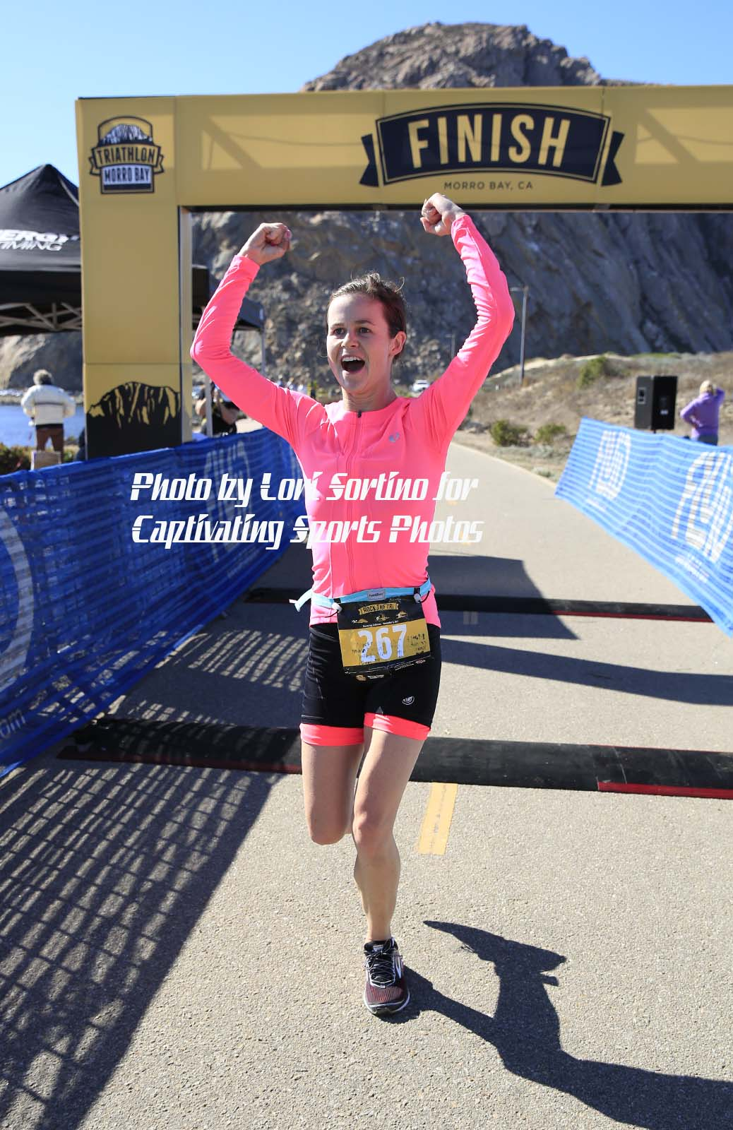 female triathlete after finish line hot pink long sleeve top celebrating